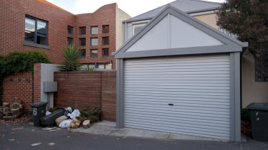 Bags of garbage litter the back gate and garage of a house where a rowdy party was held in North Melbourne.