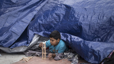 A migrant child from El Salvador plays under a tarpaulin at the El Chaparral port of Entry, in Tijuana, Mexico, on Monday.