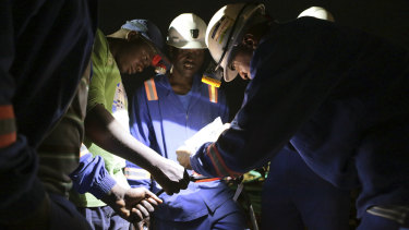 Established miners fix broken equipment used to help rescue dozens of artisanal miners, who are feared dead after rains flooded the mines last week.