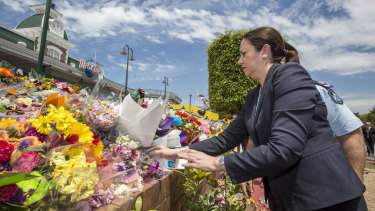 Queensland Premier Annastacia Palaszczuk places flowers at the makeshift memorial outside Dreamworld in 2016.