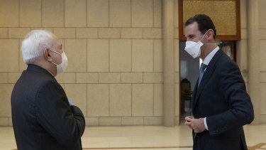 Syrian President Bashar Assad, right, wears a mask to help protect from the coronavirus, as he speaks with Iranian Foreign Minister Mohammad Javad Zarif, who also wore a mask and gloves, in Damascus, Syria.