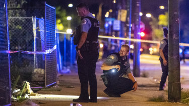 Police investigate the scene where multiple people were shot in Chicago on Saturday.