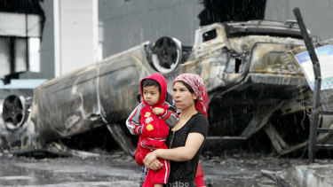 A Uighur woman and a child walk past a burnt car at a destroyed dealership  following riots in Urumqi, western China's Xinjiang province in 2009. Analysts say the riots set in motion the harsh security measures now in place.