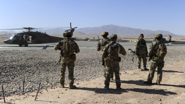 SAS soldiers on duty in Afghanistan move towards a waiting UH-60 Blackhawk helicopter.