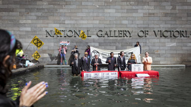 Members of Extinction Rebellion stage a protest in the water feature at the National Gallery of Victoria in Melbourne.