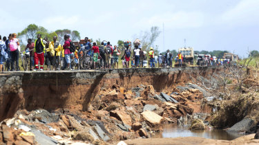 People pass through a section of the road damaged earlier this month by Cyclone Idai in Nhamatanda in Mozambique.
