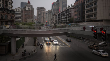 A resident crosses a road while cars wait for traffic lights on April 2 in Wuhan, Hubei, China, where residents with green health code are allowed to go out in public.