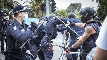 A police officer wrestles with a protester outside the National Gallery of Victoria.