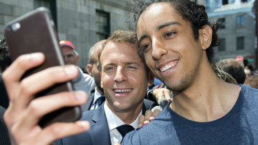 French President Emmanuel Macron, left, poses with a fan during a visit to Old Montreal, Canada.