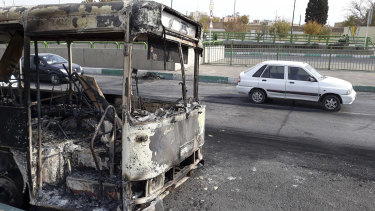 Cars in Tehran drive past a bus that was torched during protests that followed authorities' decision to raise petrol prices.