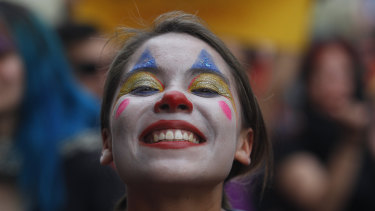 A woman made up as a clown poses during the eighth day of protests against President Sebastian Piñera's government.