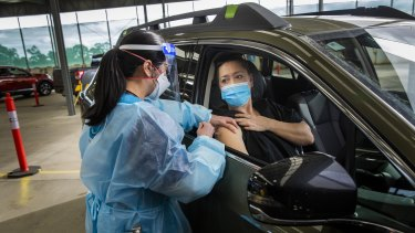 Health worker Khanh Tran  gives Nicolette Kolozsi her first Pfizer jab on Sunday at the drive-through clinic, which will officially open on Monday.