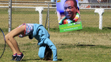A child plays next to Zimbabwean President Emmerson Mnangagwa's election campaign poster during a rally organised for the white community in Harare on Saturday.