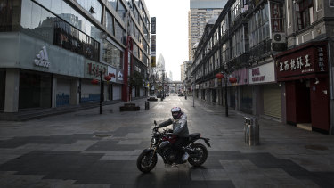A man rides a motorcycle in an empty business street in Wuhan, Hubei province, China.