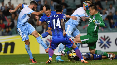 Shanghai goalkeeper Qiu Shengjiong and his teammates manage to block Alex Brosque.