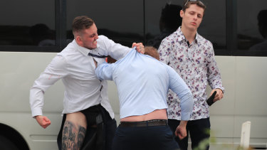 A Rosehill patron looks unimpressed as two  brawlers go toe to toe.