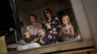 The Mitcham family - Ashley, Lindsay,  Jane 7, Francis 4 and Dominic 3 - watch the Easter Sunday Mass on their television.