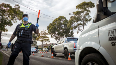 Police at a road block enforce lockdowns in one of 10 Melbourne postcodes after a spike in coronavirus cases.