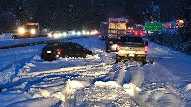 """Cars and trucks in stopped traffic on Interstate 5 near Dunsmuir, California, after a """"bomb cyclone"""" cause temperatures to drop suddenly."""