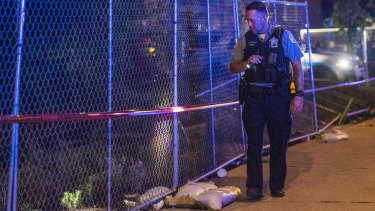 An officer scours a scene of one of several shootings in Chicago over the weekend.
