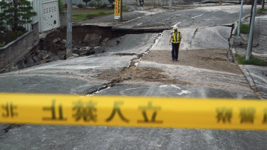 A security guard walks on an earthquake-damaged street in Kiyota, outskirts of Sapporo.