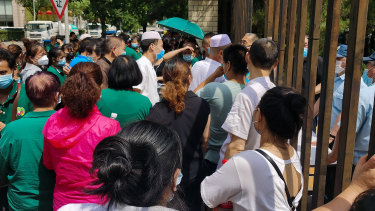 Citizens who visited or live near Xinfadi Market queue for a nucleic acid test at a sports centre in Beijing.