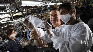 Nobody denim co-founder John Condilis inspects a mask prototype with cutting machinist K Yokachanthiran. The company is hoping to win a government PPE contract to save jobs.