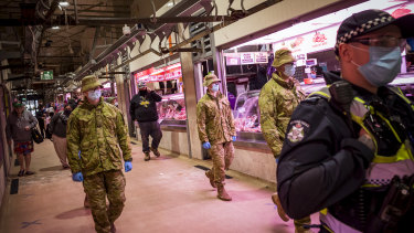 Members of Victoria Police, aided by ADF soldiers, patrol the Queen Victoria Market.