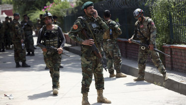 Afghan security personnel gather near the prison.