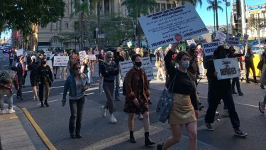 """Protesters march through the Brisbane inner city towards the Home Affairs office, with chants of """"no hate, no fear, refugees are welcome here""""."""