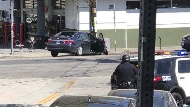 Police officers stand guard near a crashed vehicle outside a Trader Joe's store in Los Angeles on Saturday.