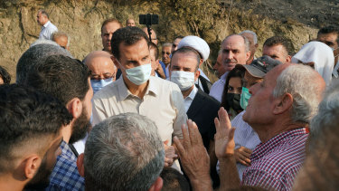 Syrian President Bashar Assad speaks with people during his visit to the coastal province of Latakia, Syria after the wildfires in 2020.