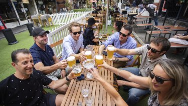 A group of friends gather to celebrate the easing of restrictions at Yarraville on Friday.