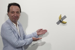 Gallery owner Emmanuel Perrotin poses next to Maurizio Cattlelan's 'Comedian' at the Art Basel exhibition in Miami Beach, Florida. The work sold for $US120,000 – and was also eaten.