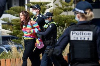 Police arrest a protester in St Kilda on Saturday.