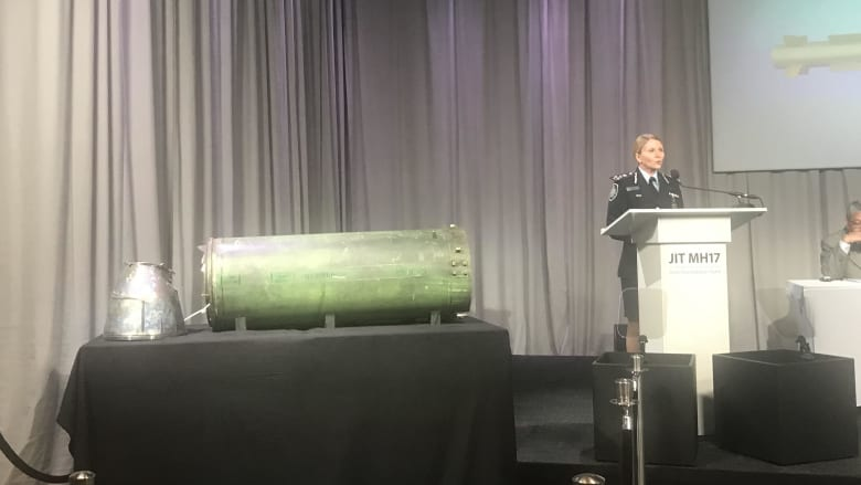 AFP commander Jennifer Hurst shows the missile that allegedly shot down MH17 at a press conference in the Netherlands.