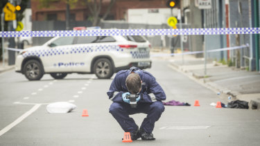 An officer photographs evidence left at the scene of the fatal Love Machine nightclub shooting in Prahan.