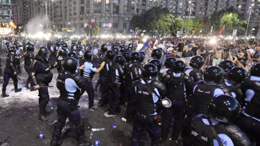 Riot police charge to clear the square during protests outside the government headquarters in Bucharest.