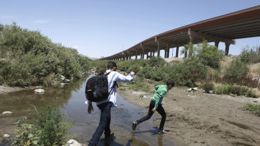 People cross the Rio Grande from Chihuahua, Mexico, into the US to turn themselves over to authorities and ask for asylum.