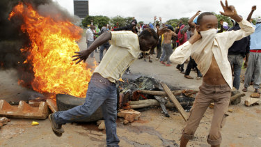 """Protesters gather near a burning tire during a demonstration over the hike in fuel prices last week. The President has returned to Zimbabwe, seeking to restore """"calm""""."""