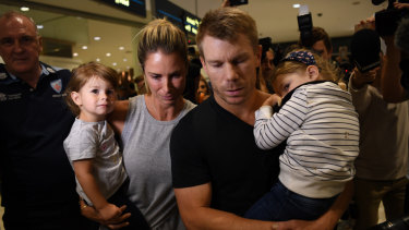 In the eye of the storm: Dave Warner and his family arrive back in Sydney in the wake of the Cape Town ball-tampering scandal.