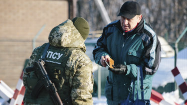 A Ukrainian border guard checks documents of a man who is going to cross the border to Russia at the checkpoint  with Russia in Hoptivka, Ukraine, on Friday.