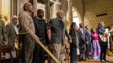 Elected officials, civic leaders and clergy join arms and sing together at the conclusion of an Interfaith Vigil of Solidarity and Hope at Rodeph Shalom in Philadelphia on Sunday.