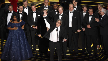 Peter Farrelly (center) and the cast and crew of <i>Green Book</i> accept the award for best picture.