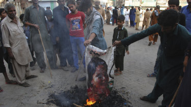 Pakistani protesters burn a poster image of a Christian woman, Asia Bibi, who has spent eight-years on death row accused of blasphemy and been acquitted by a Supreme Court, in Hyderabad, Pakistan.
