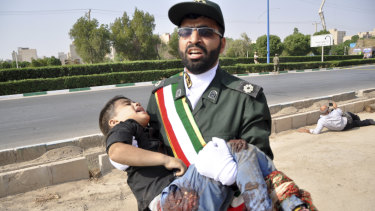A Revolutionary Guard member carries a wounded boy after a shooting during a military parade marking the 38th anniversary of Iraq's 1980 invasion of Iran.