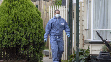 A forensic officer searches the home in Phair Court, Altona, where two people were arrested.