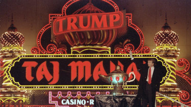 Donald Trump stands next to a genie lamp as the lights of his Trump Taj Mahal Casino Resort mark its grand opening in 1990.