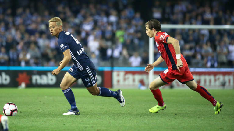 Keisuke Honda of the Victory runs away from Craig Goodwin of Adelaide United.