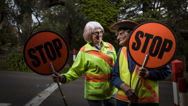 Lollipop ladies Pam Pryor (left) and Pam Ramadge have been supervising crossings on opposite sides of Melbourne for 45 years.